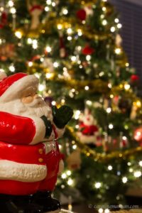 Santa shot in front of a Christmas tree, with a narrow aperture.