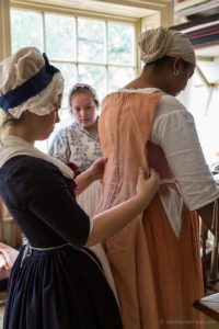 A seamstress fits a garment in the Milliner's Shop in Colonial Williamsburg.