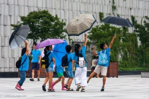 Wind catches the umbrellas of a group of Korean children at the National Museum.