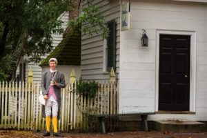 Pausing in front of the cobbler shop, a colonial gentleman holds his mug.