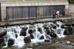 A couple walks past a waterfall along the Cheonggye Stream in Seoul, South Korea.