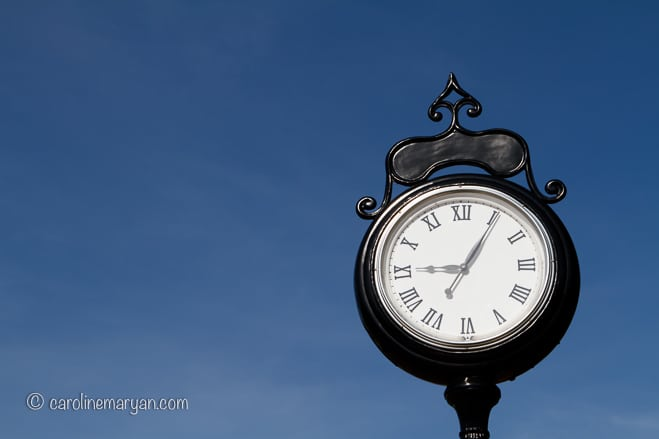 An old street clock against a blue sky with wispy clouds