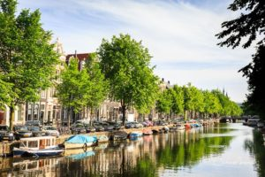 Boats tied up along the Keizersgracht Canal in Amsterdam, in early light.