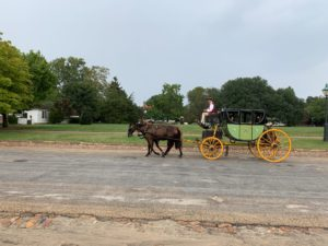 A horse-drawn carriage is driven along Duke of Gloucester Street in Colonial Williamsburg.