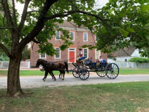 A horse-drawn carriage is driven in front of the George Wythe House in Colonial Williamsburg. We can see the head of the driver.