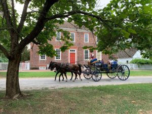 A horse-drawn carriage is driven in front of the George Wythe House in Colonial Williamsburg. The head of the driver is hidden by the tree leaves.