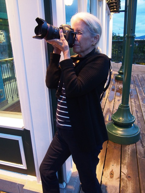 Photo of a woman holding a camera and bracing herself against a wall