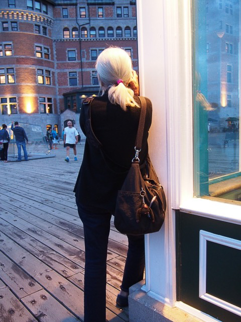 Photo of a woman leaning against a wall while holding a camera, shot from the rear