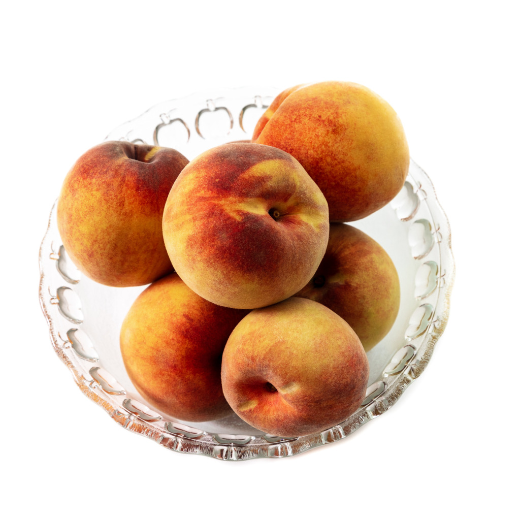 A Bowl of Peaches in a Glass Bowl Isolated on a White Background