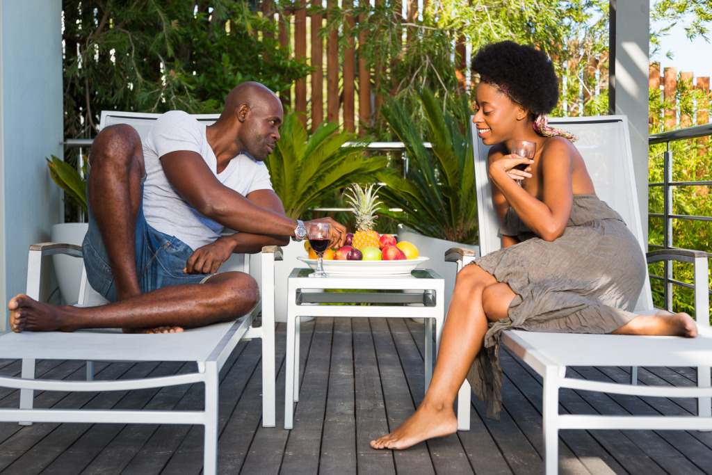 Couple sharing wine and fruit on vacation in the tropics.