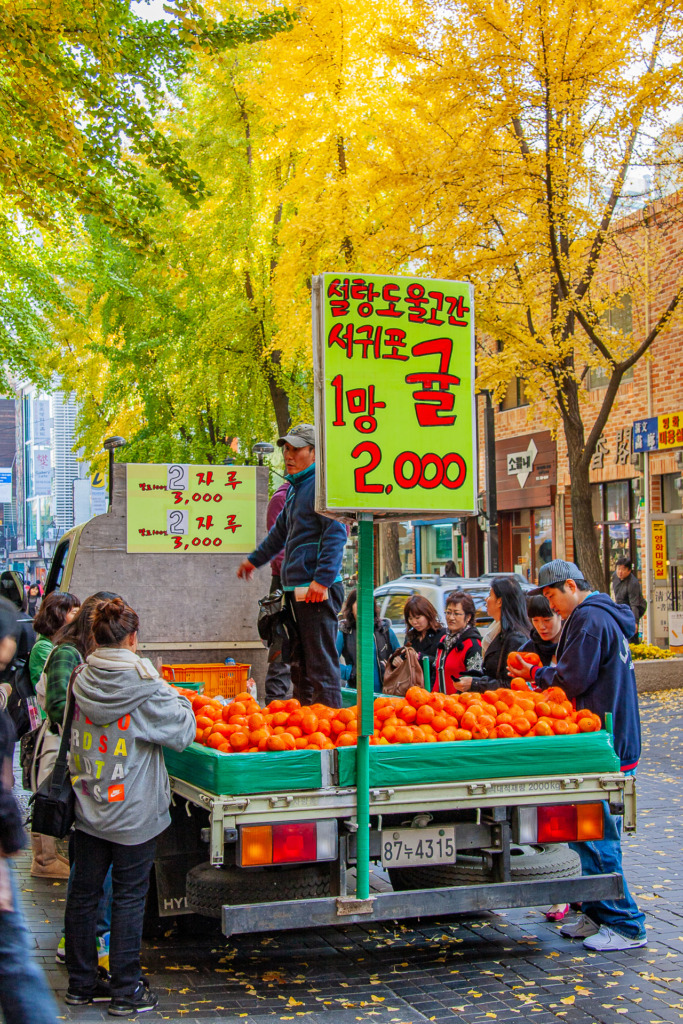 the colors of fall are captured in this photo of a tangerine truck in Insadong in the fall
