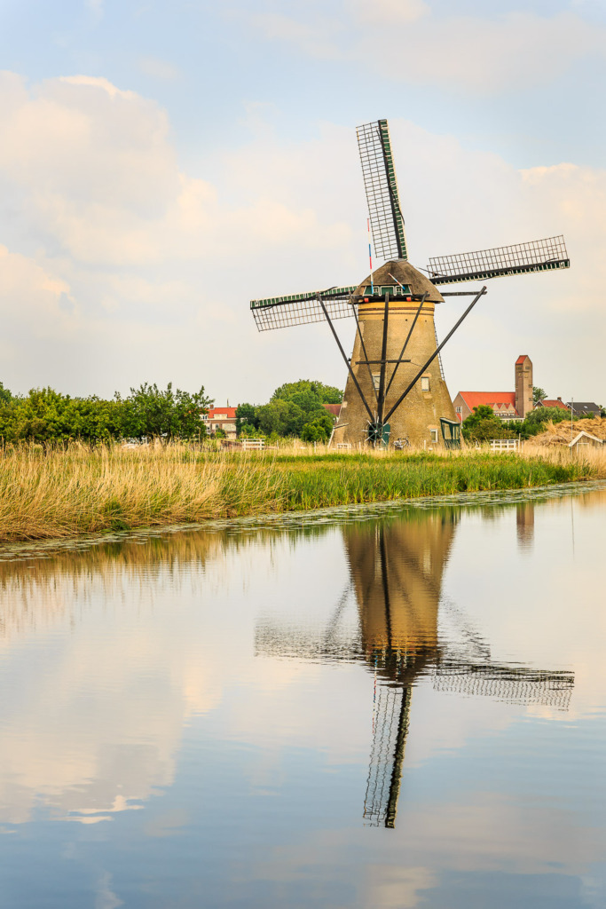 An old windwill along a canal in Kinderdijk, Netherlands with re